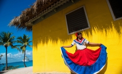 Catalina_Island_Dominican_Republic._A_woman_in_traditional_outfit_in_front_of_a_bungalow_on_a_seashore_full_length_portrait-1024x681